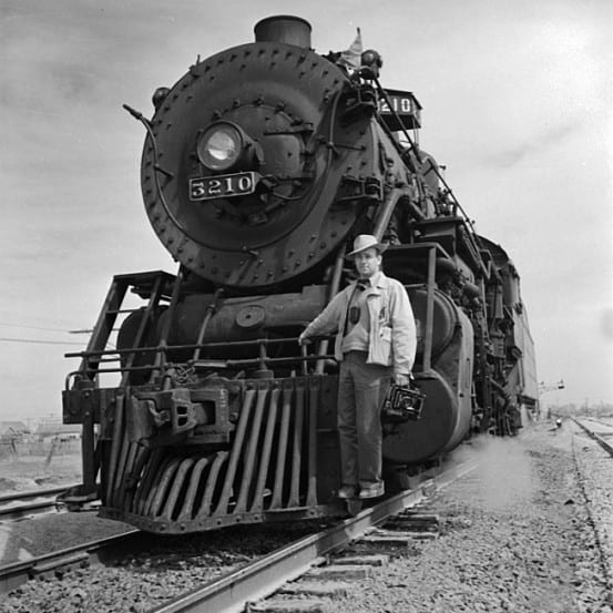 Portrait of photographer Jack Delano and a locomotive