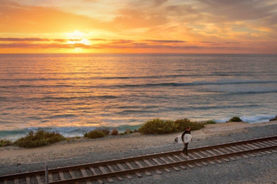 Surfer crosses the tracks at sunset in Del Mar