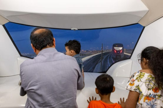 Passengers enjoy the view from the end of the train