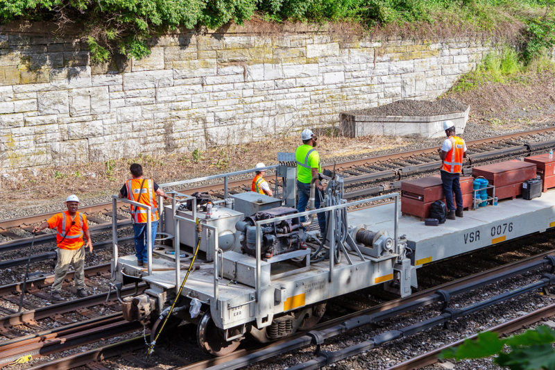 The work crew prepares to unload the rail