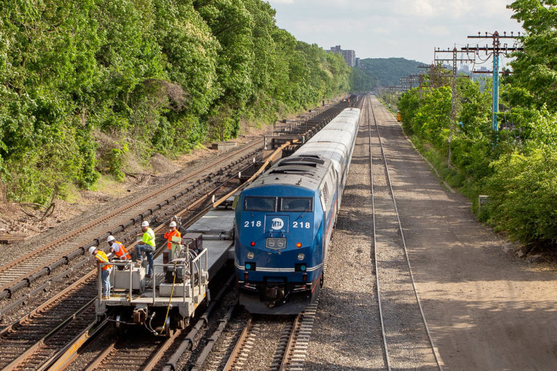 A train passes as the rail train crew keeps watch of the unloading piece of rail