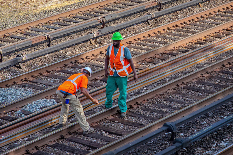 Two workers ensure the dropped rail is straight in between the tracks