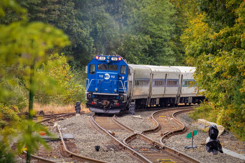 The departing train passes the black bagged signals
